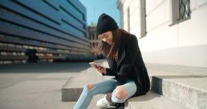 Stående av den unga afrikansk amerikankvinnan som använder telefonen, utomhus Royaltyfria Foton