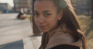 Stående av den unga afrikansk amerikankvinnan som ser till en kamera, utomhus långsam rörelse Arkivbilder