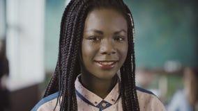 Stående av den unga afrikanska kvinnan som ser kameran och ler på det upptagna moderna kontoret Lyckad anställd på arbete Royaltyfria Foton