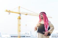 St?ende av den unga arabiska aff?rsmannen som rymmer portf?ljen och st?r p? konstruktionsplats med kranbakgrund arkivbilder