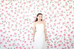Stående av den unga asiatiska bruden som ler på kameran, rosa rosor och royaltyfria bilder