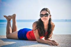 Stående av den unga asiatiska seende kvinnalögnen nära simbassäng på den tropiska stranden på Maldiverna Fotografering för Bildbyråer