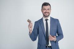 Stående av den unga attraktiva affärsmannen med att le blick som rymmer trähårkammen Stilfull skäggig barberare i dräkt som kamma fotografering för bildbyråer