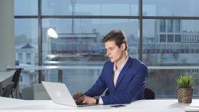Stående av den unga attraktiva affärsmannen som arbetar på ett skrivbord, bruksbärbar dator i kontoret lager videofilmer