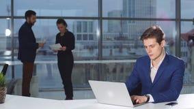 Stående av den unga attraktiva affärsmannen som arbetar på ett skrivbord, bruksbärbar dator i kontoret stock video