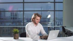Stående av den unga attraktiva affärsmannen som i regeringsställning arbetar på ett skrivbord, bruksbärbar dator lager videofilmer