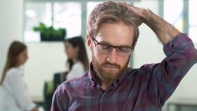 Stående av den unga attraktiva allvarliga grabben som i regeringsställning trycker på hans hår på bakgrunden av två hans kollegor stock video