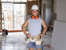Stående av den unga attraktiva byggmästaremannen på hans 20-tal som poserar lycklig säkert och stolt på helme för skydd för konst Royaltyfri Bild