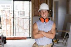 Stående av den unga attraktiva byggmästaremannen på hans 20-tal som poserar lycklig säkert och stolt på helme för skydd för konst Royaltyfri Foto