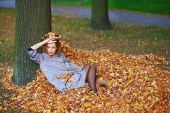 Stående av den unga attraktiva flickan med gulingsidor i hennes hår på höstbakgrund Royaltyfri Foto