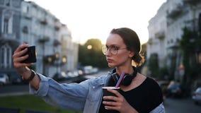 Stående av den unga attraktiva kvinnan i solexponeringsglas med hörlurar på halsen som poserar på kameran i stadsgatan close stock video