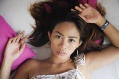 Stående av den unga attraktiva och härliga asiatiska kvinnan som ligger på säng på sovrummet som poserar sexigt se till kameran i Fotografering för Bildbyråer