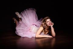 Stående av den unga ballerinaflickan för härlig passform i rosa tillfälliga och balettkläder royaltyfri foto