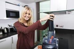 Stående av den unga blonda kvinnan som använder juiceren för juicing morötter i kök Arkivfoton