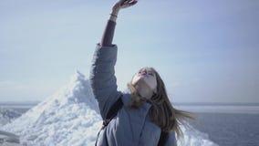 Stående av den unga blonda nätta kvinnan i varmt omslag som går på glaciären som rymmer hennes mobiltelefon i den lyftta handen s arkivfilmer
