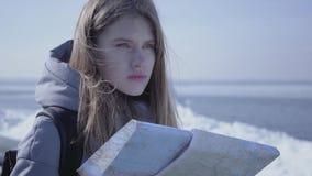Stående av den unga blonda nätta kvinnan i varmt omslagsanseende på glaciären med översikten i händer som omkring ser _ arkivfilmer
