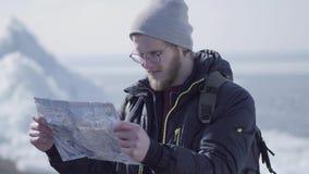 Stående av den unga blonda skäggiga stiliga mannen i varmt omslags- och hattanseende på glaciären som kontrollerar med översikten stock video