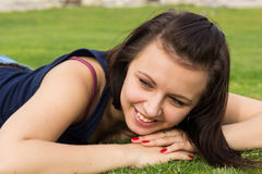 Stående av den unga brunettflickan som ligger på ett gräs royaltyfria foton