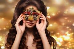 Stående av den unga brunettkvinnan i en guld- maskering på en guld- bakgrund royaltyfri fotografi