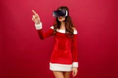 Stående av den unga brunettkvinnan i röd sammetklänning genom att använda virtuell verklighethörlurar med mikrofon Arkivbilder