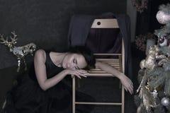 Stående av den unga brunettkvinnan i sovande nolla för aftonsvartklänning royaltyfri foto