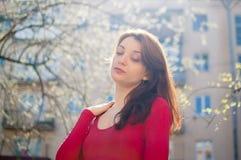 Stående av den unga brunettkvinnan med sinnliga kanter i röd skjorta som utomhus tycker om vårbris, medan solen skiner arkivbild