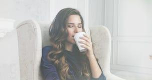 Stående av den unga brunhåriga kvinnan som dricker kaffe i morgonen stock video