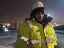 Stående av den unga byggnadsarbetaren i hjälm på natten Arkivbilder