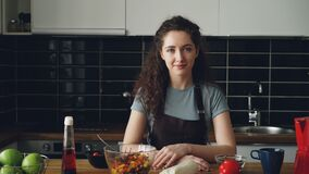 Stående av den unga caucasian kvinnan för utövande kock i förklädesammanträde på tabellen i modernt lighty rymligt kök som ler stock video