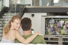 Stående av den unga Caucasian kvinnan med hållande ögonen på film för man på television i vardagsrum Arkivfoton