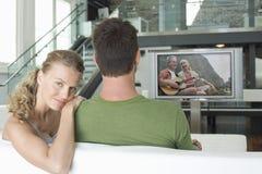 Stående av den unga Caucasian kvinnan med hållande ögonen på film för man på television i vardagsrum Royaltyfri Bild