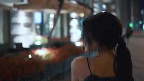 Stående av den unga charmiga flickan i nattstaden Sikten från baksidan långsam rörelse arkivfilmer
