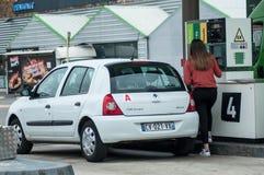 Stående av den unga chaufförflickan som tar bränsle i den Intermarche bensinstationen arkivfoton