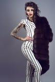 Stående av den unga chic mörker-haired tatuerade damen som bär den stilfulla randiga overallen med korta muffar och den storartad fotografering för bildbyråer