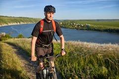 Stående av den unga cyklistridningmountainbiket som är stigande ovanför den härliga blåa floden Royaltyfria Bilder