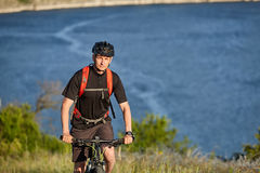 Stående av den unga cyklistridningmountainbiket som är stigande ovanför den härliga blåa floden Royaltyfri Foto