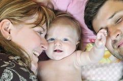 Stående av den unga familjen med gulligt little som är babby Arkivfoton