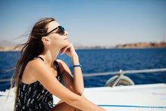 Stående av den unga fantastiska flickan i solglasögon som bär hattsammanträde på yachten arkivbild
