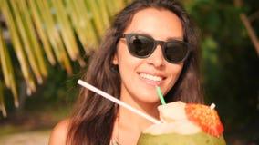 Stående av den unga flickan för blandat lopp som dricker den nya thailändska kokosnötvattencoctailen på den tropiska stranden 4K  stock video
