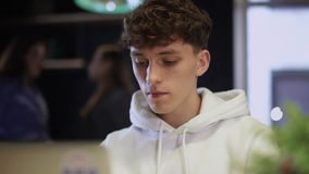 Stående av den unga fokuserade grabben som framme arbetar av en bärbar dator och dricker kaffe från papperskoppen stock video