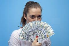 Stående av den unga glade affärskvinnan som rymmer amerikanska dollarräkningar arkivbilder