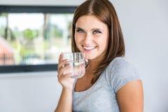 Stående av den unga gladlynta kvinnan med exponeringsglas av mineralvatten Arkivbild