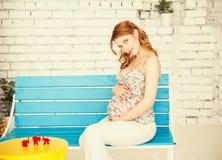 Stående av den unga gravida kvinnan Arkivfoto