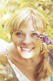 Stående av den unga gulliga le kvinnan med en bukett av blommor Naturskönhet, romantiker, fjädrar välkomnande begrepp Fotografering för Bildbyråer