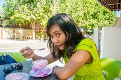 Stående av den unga härliga asiatiska flickan som äter glass på det utomhus- kafét och ser kameran Arkivfoto