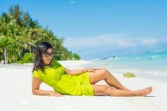 Stående av den unga härliga asiatiska flickan som lägger på stranden och ser kameran Arkivbilder