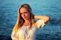 Stående av den unga härliga blonda flickacloseupen på havsbakgrunden Arkivfoton