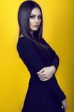 Stående av den unga härliga brunetten med yrkesmässigt smink och långt rakt skinande hår som bär den svarta klänningen Royaltyfri Foto
