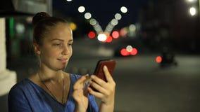 Stående av den unga härliga caucasian kvinnan som använder smarta den utomhus- telefonhandhållen i stadsnatten som ler, framsida lager videofilmer
