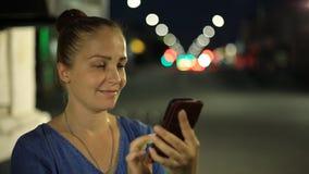 Stående av den unga härliga caucasian kvinnan som använder smarta den utomhus- telefonhandhållen i stadsnatten som ler, framsida stock video